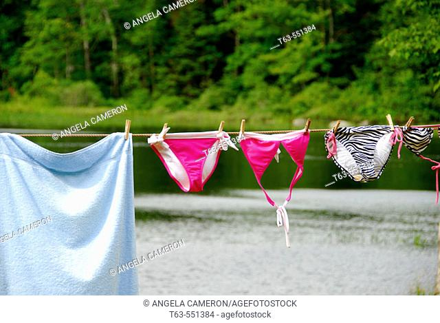 teen age girls swimsuits hanging on clothesline at the lake