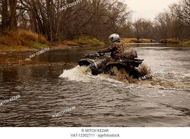 Hunter Going Through Creek On Atv
