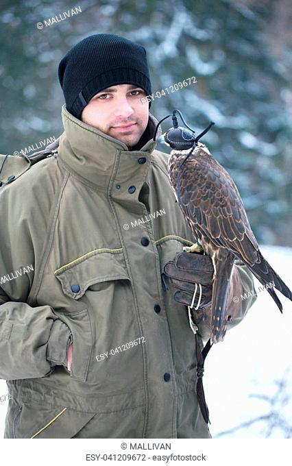 Young handsome man holding a falcon on his arm