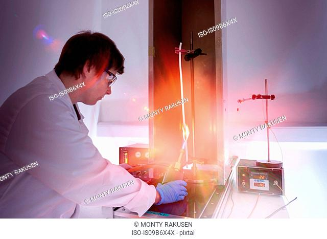 Scientist testing electrical cable for flammability in flame test in electrical cable laboratory