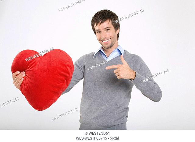 Young man holding heart-shaped cushion, smiling,portrait