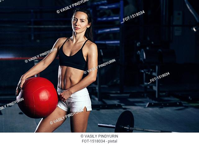 Portrait of young woman holding medicine ball at gym