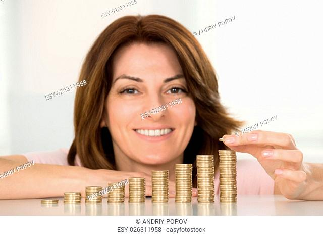 Young Happy Woman Stacking Coins At Desk