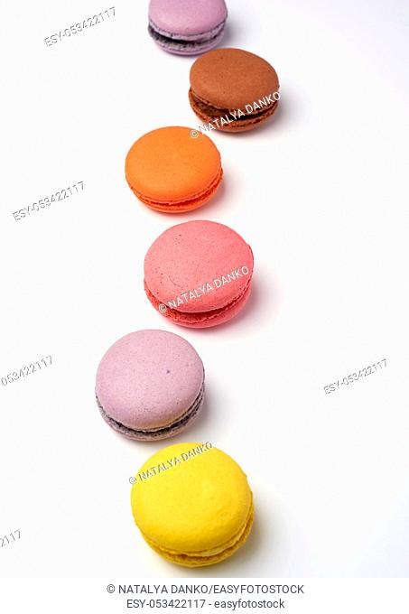 multi-colored baked macaroons from almond flour on a white background, selective focus