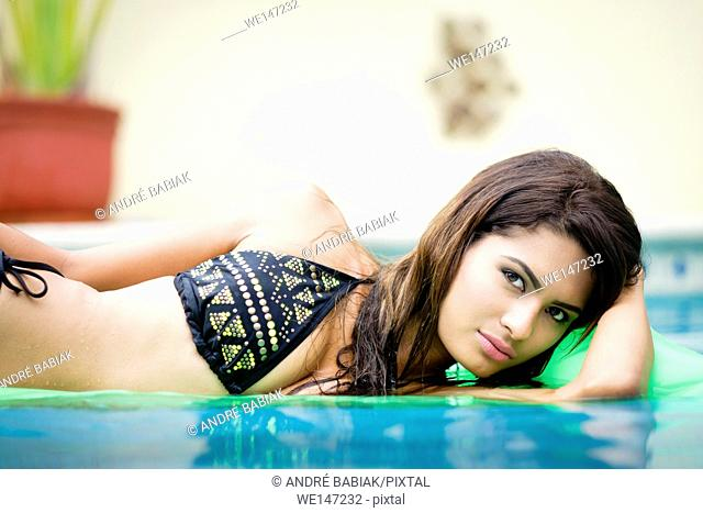 Young attractive hispanic woman looking at camera while floating on air mattress in swimming pool