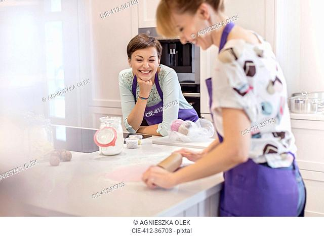Female caterers baking, using rolling pin in kitchen