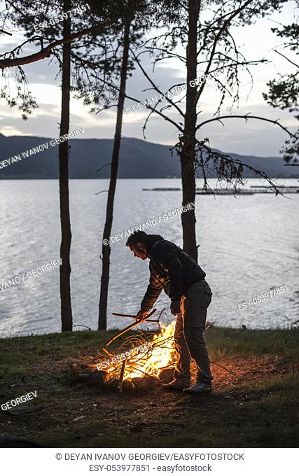Man lights a fire in the fireplace in nature at night