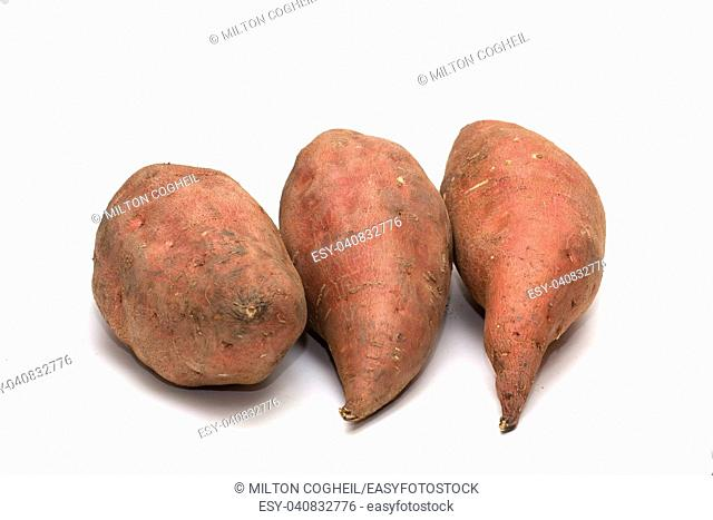 An arrangement of raw sweet potato tubers on a white background