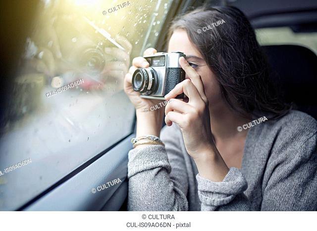 Woman photographing out of car window