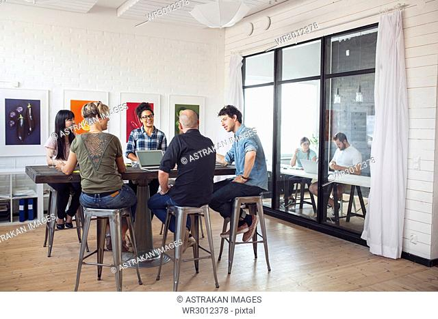 Coworkers talking in office, other working in background