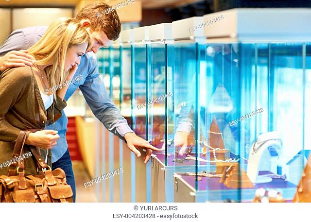 Attractive young couple looking at jewellery in display cabinets