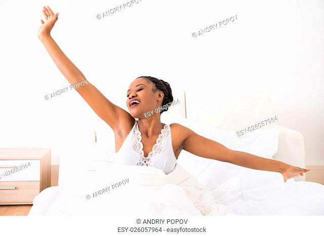 Portrait Of A Young African Woman Stretching Her Arms On Bed
