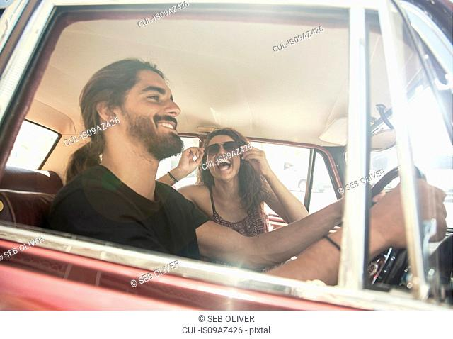 Young couple driving vintage car, Cape Town, South Africa