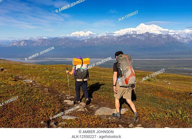Woman and man backpacking on the tundra towards Denali and the Alaska Range, along the Kesugi Ridge Trail, Denali State Park, on a sunny autumn day
