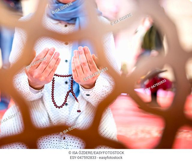 View through fence:Muslim woman in headscarf and hijab prays with her hands up in air while holding rosary in mosque. Religion praying concept