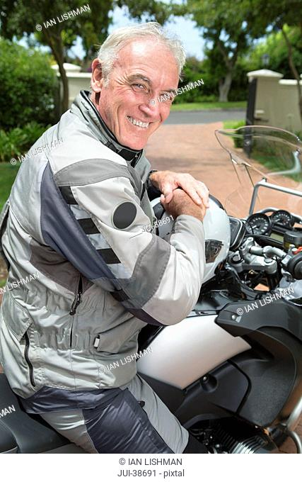 Portrait of happy senior man on motorcycle in driveway