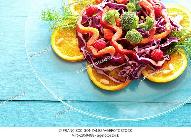 Mixed salad on glass plate on wooden background