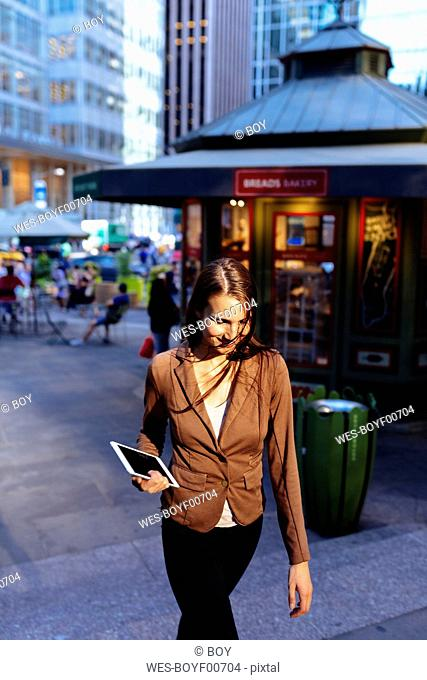 USA, New York, Manhattan, smiling young businesswoman with tablet in the evening