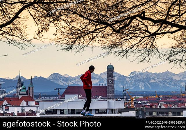 25 February 2020, Bavaria, Munich: A jogger stands on Luitpold Hill in the Schwabing district against the backdrop of the Bavarian capital