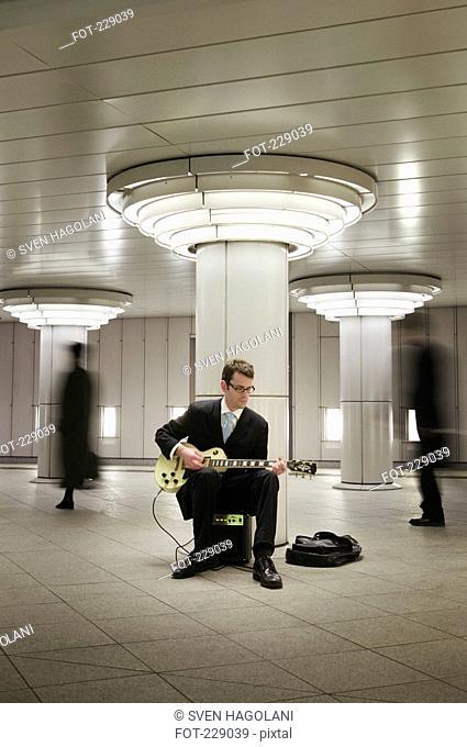 Businessman sitting in subway station busking, Tokyo, Japan