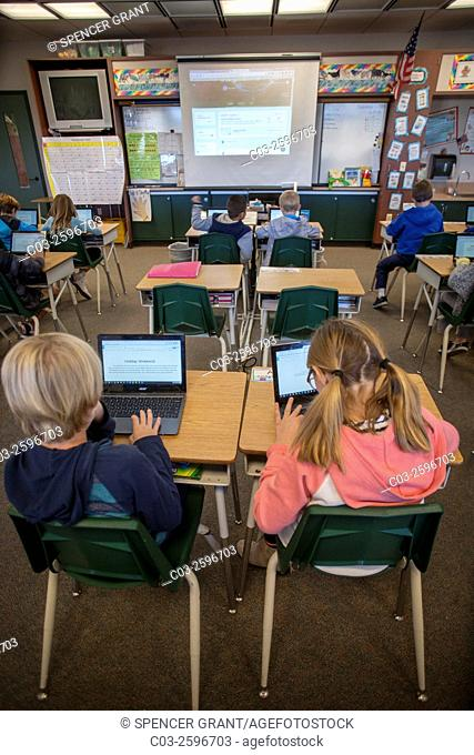 Third grade students enter information in their Google Chromebook laptop computers in a San Clemente, CA, elementary school classroom