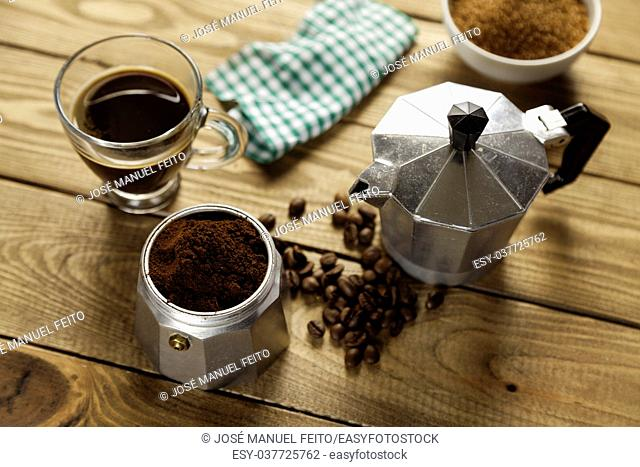 Italian coffee maker, napkin, brown sugar bowl, cup of coffee and coffee beans on wood table