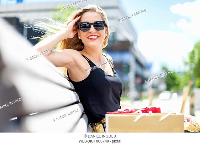 Portrait of smiling young woman wearing sunglasses sitting on a bench with shopping bags