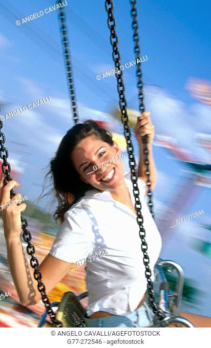 Woman on wave swinger carousel in amusement park. Florida. USA
