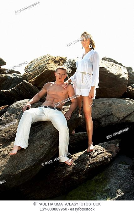 Caucasian guy and girl together on rock formation  Female is wearing long white shirt and holding sunglasses, standing on rocks  Guy showing muscular abs and...