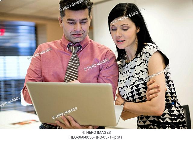 Businessman with female colleague using laptop in office