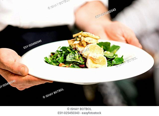 Chef holding a salad of roast goat cheese