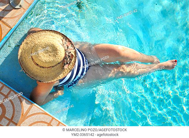 Woman in a hat resting and enjoying a swimming pool