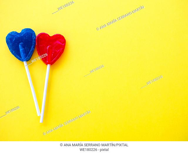 Blue and red lollipop on a yellow background