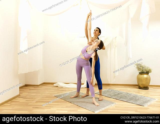 young girl is engaged with a yoga coach in the studio