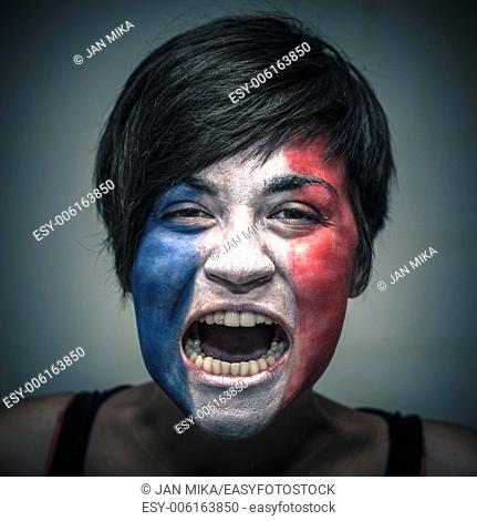 Portrait of angry woman with flag of France painted on face