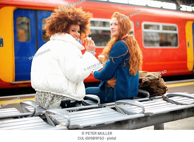 Friends on bench on train station platform, London