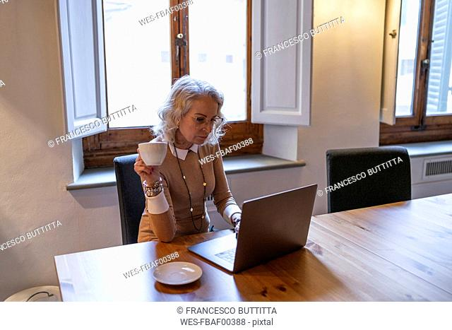 Mature businesswoman sitting at table with cup of coffee using laptop