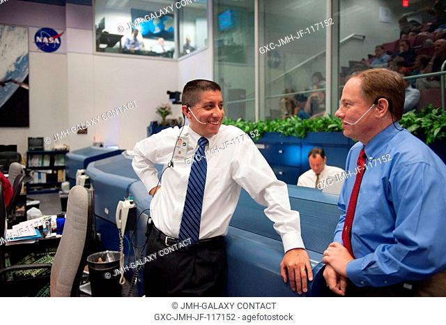 In the shuttle flight control room in JSC's Mission Control Center in Houston, STS-135 ascent flight director Richard Jones (left), talks with John McCullough