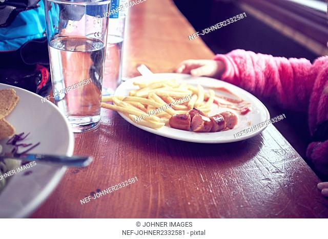 Sausage and chips on plate