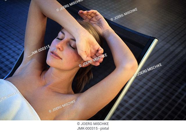 young woman relaxing, lying, on a deck chair in a rest room, chill-out room of a spa