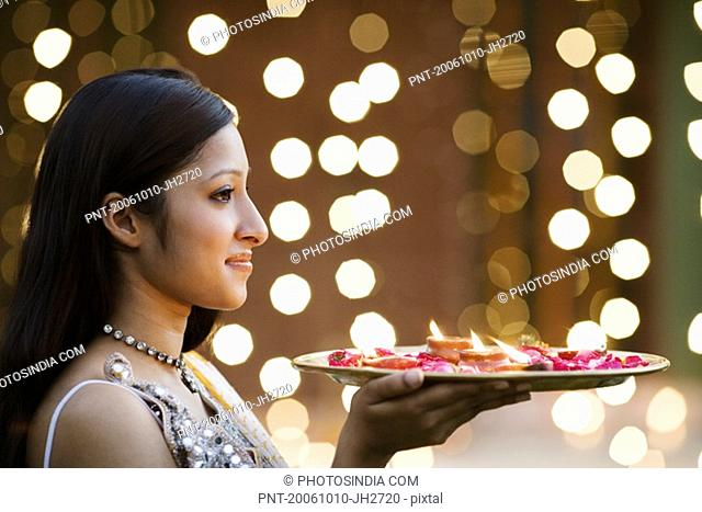 Side profile of a young woman holding oil lamps and Rose petals in a plate