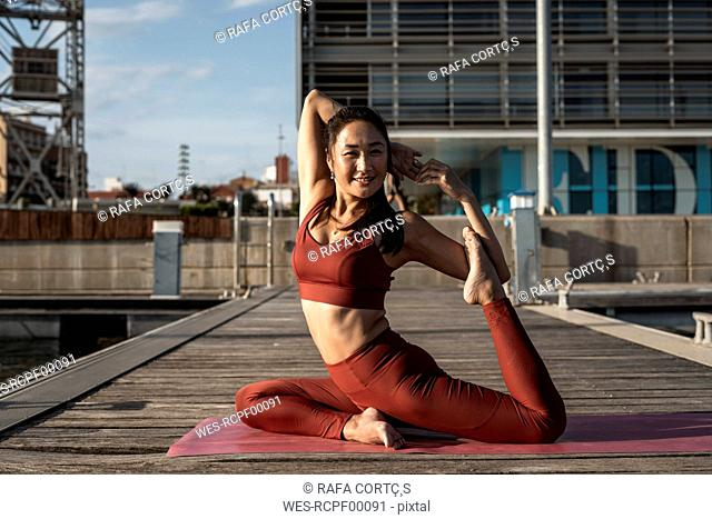 Asian woman practicing yoga on a pier, swan pose
