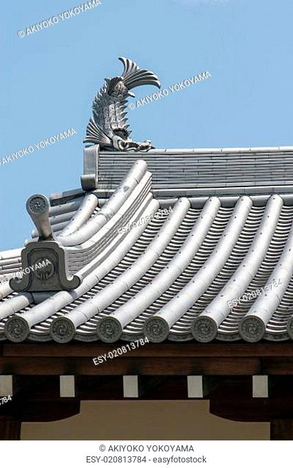 Japanese temple roof tiles against blue sky