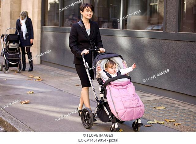 Two mothers pushing their strollers in the street