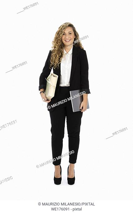 Businesswoman standing in the studio with computer and documents under her arms, she is wearing a black suit and a white shirt