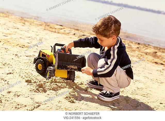 portrait, full-figure, 6-year-old boy with brown hair wearing black jacket with white stripes, khaki trouser and black sneakers plays with his yellow truck in...