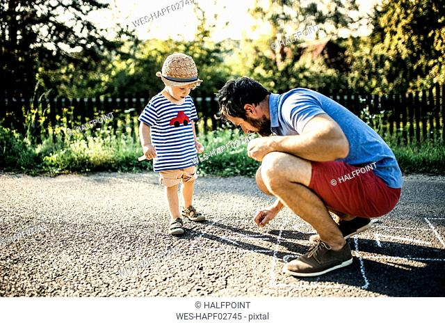 Father drawing Hopscotch on asphalt while his little son watching him