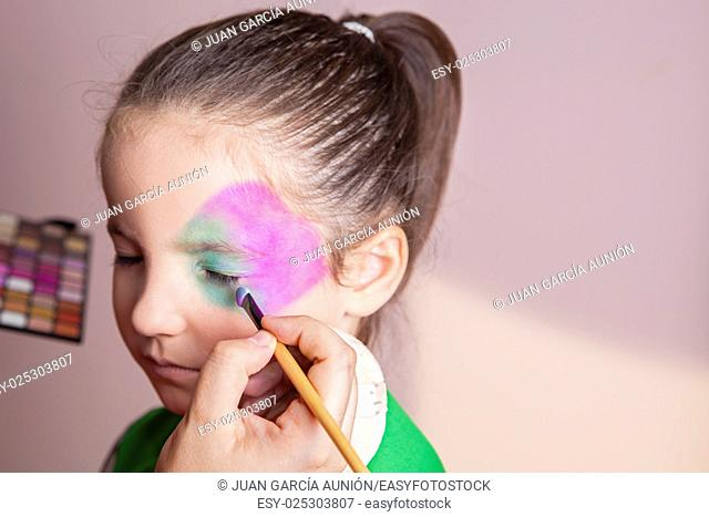 Little cute girl making facepaint before halloween party. The make-up artist is applying some colors