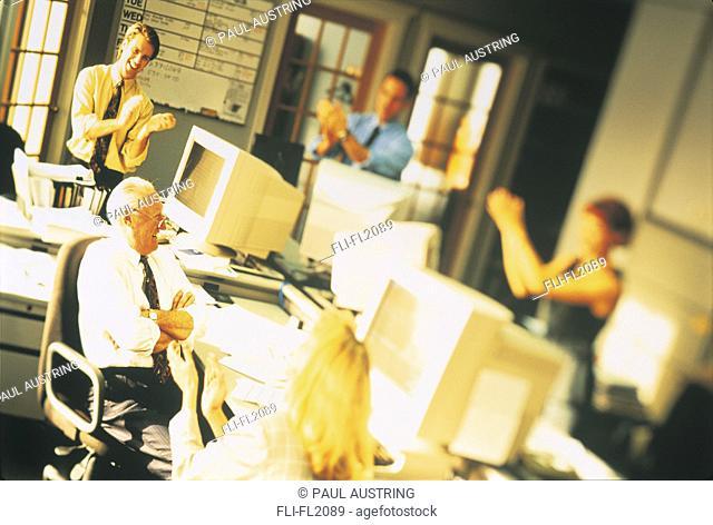 Executives applauding senior executive at work station