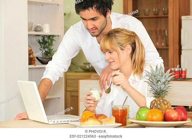 Couple with laptop having breakfast
